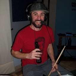 Ian smiling broadly with a beer behind his drumset.