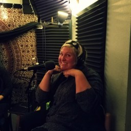 Michelle posing for the camera in the studio recording for the Worst Little Podcast.
