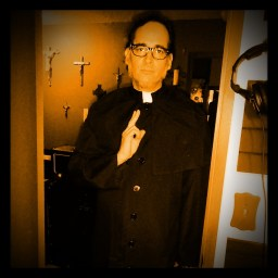 Host of the Worst Little Podcast, Nick Ramirez dressed as a priest is blessing the studio.