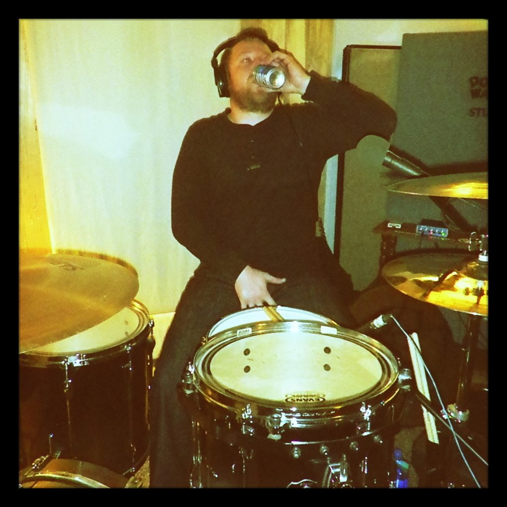 Garett, drummer for Reno metal band Kanawha posing with his set at Dogwater Studios.