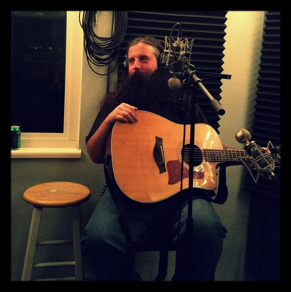 Reno folk americana musician Josiah Knight looking wistfully while holding his guitar at Dogwater Studios.