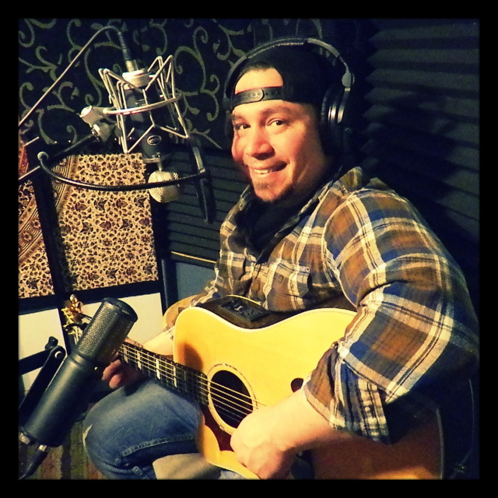 Anthony Vairetta of Reno country band Huckleberry Road posing with his guitar and smiling for the camera.