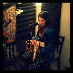 Michelle Bell of the Grimtones playing her guitar at Dogwater Studios.