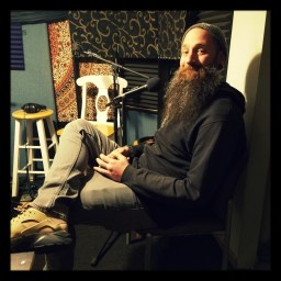RV of Almond Mocha Music relaxes in a chair at Dogwater Studios in Reno, Nevada.