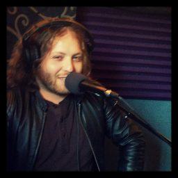 Greg Gilmore smiling in the studio.