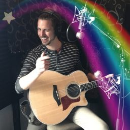 """Scott Turek, winking and pointing a finger at the camera in a """"cool guy"""" pose under a cartoon star and rainbow"""