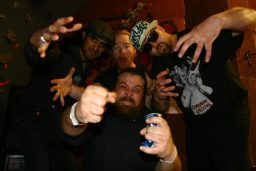 group picture of the band, with all the guys reaching forward with curled hands and grimaces on their faces.