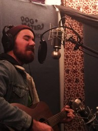 Zack Ryan sings into microphone and plays guitar at Dogwater Studios in Reno Nevada.