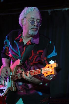 Steve Funk, Reno radio legend, in a multi-colored shirt playing a bass guitar.