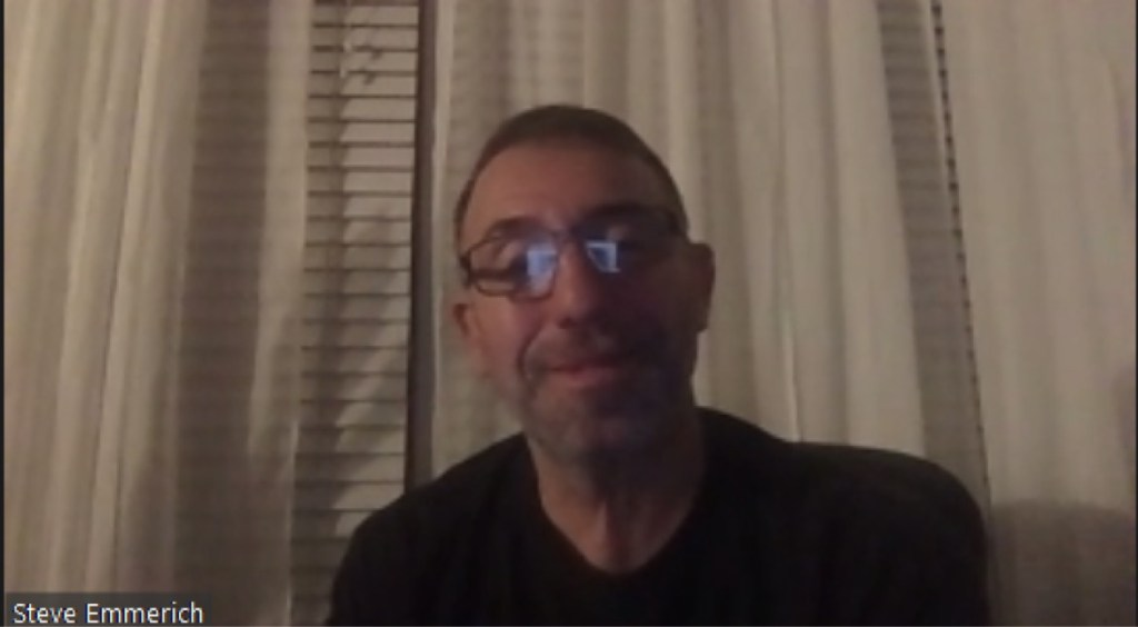 A smiling Steve Emmerich wearing glasses and a black t-shirt in his home in front of blinds-covered window