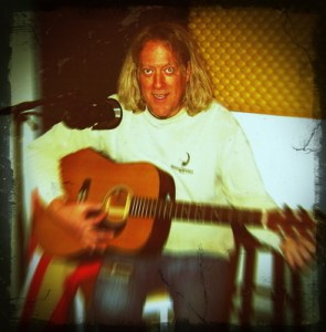 Max Volume tuning up his acoustic guitar in an image that is blurred, except for his face.