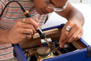 man using soldering iron to repair a speaker
