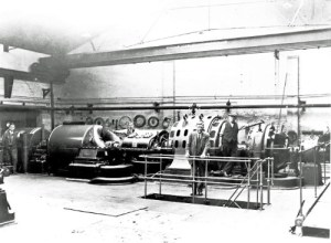SWEHS 17.0.030.jpg - Date 1930 - St James Street generating station 3.5 MVA 6.6kV turbo alternator (last set still to be installed). Mr A J Howard, Chief Engineer in foreground. Somerset, Taunton .