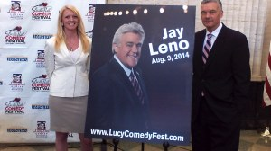 Lucy - Desi Center Executive Director Journey Gunderson (left) and Board President Tom Benson stand next to a poster announcing Jay Leno as the headline act for the 2014 Lucille Ball Festival of Comedy.