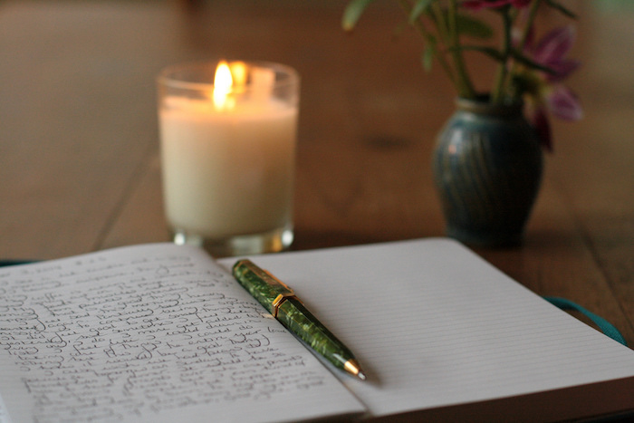 Journal and pen with a burning candle.