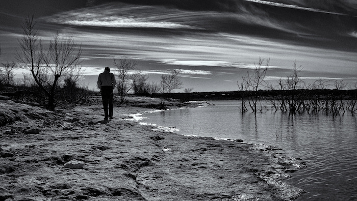 Man walking on the shore of a lake. Black and white photograph.