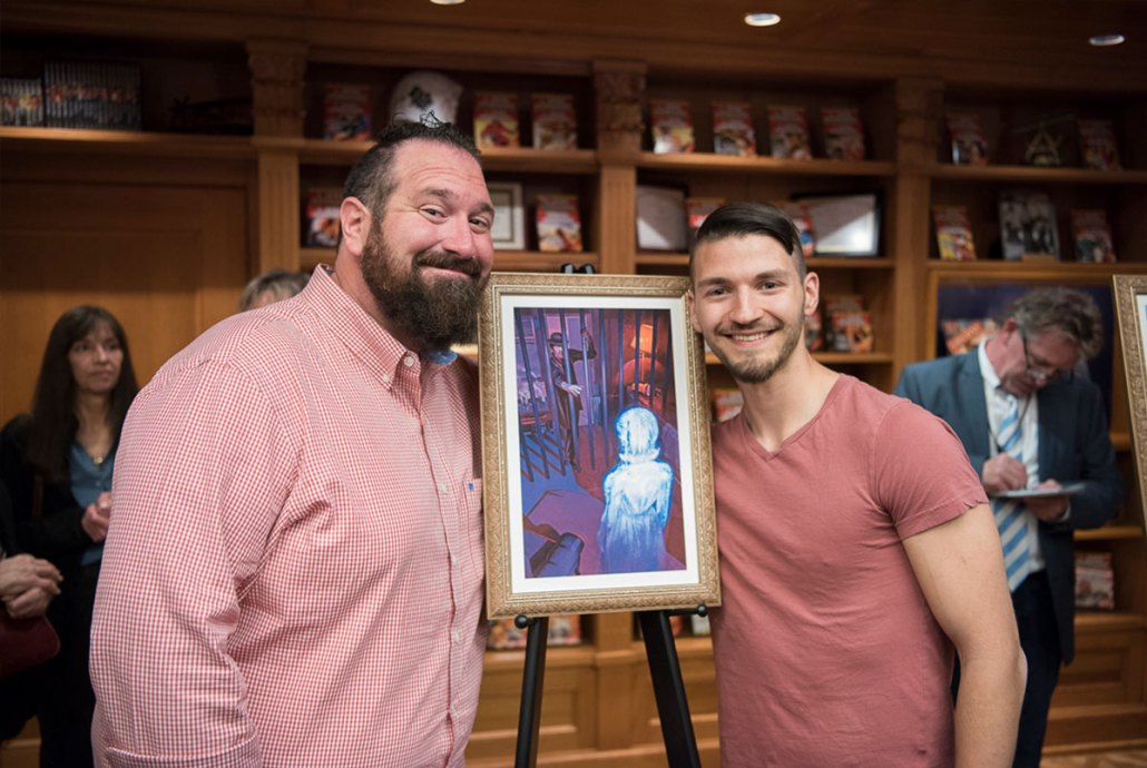 "Jake (L) with artist Ryan Richmond and the illustration for his story, ""Acquisition"""