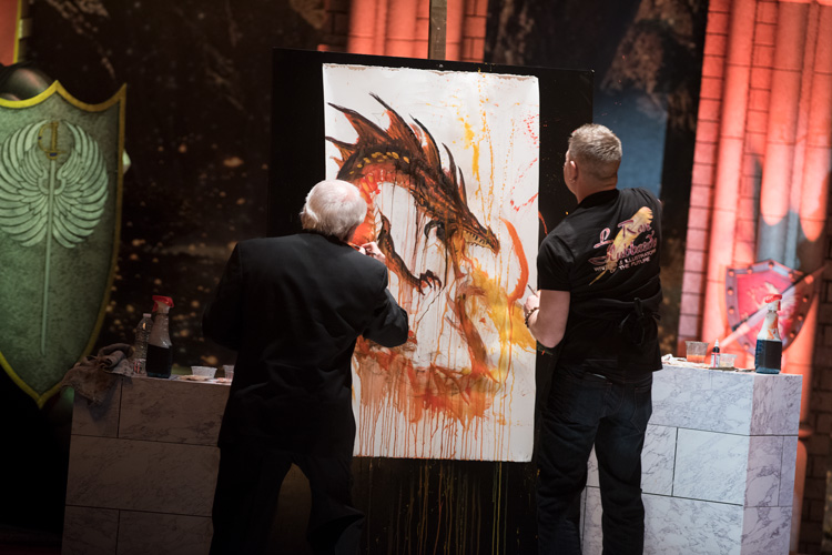 Larry Elmore & Rob Prior onstage painting a dragon at the Writers of the Future Vol 33 awards ceremony