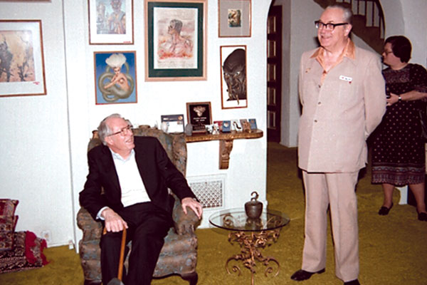 """Forrest J. Ackerman gives a tour of his famous """"Ackermansion."""" Jack Williamson, seated."""