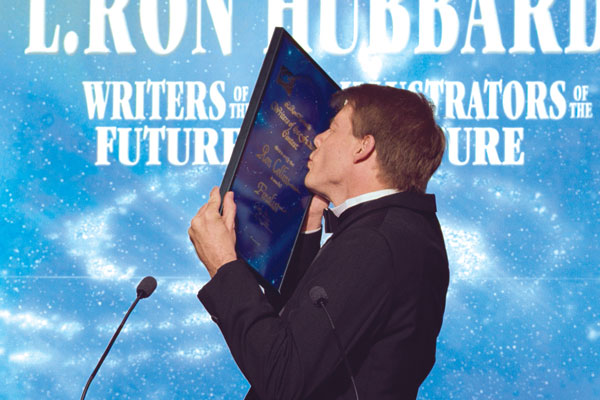 Ron Collins kisses his award.