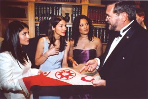 At the reception, Stephen D. Nagiewicz shows off the Explorers Club flag to actresses Marisol Nichols, Denice Duff and Gina St. John.