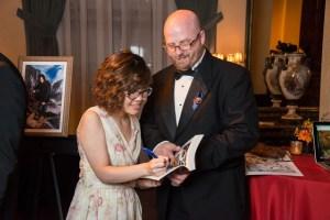 Illustrator winner Chan ha Kim autographs her artwork for Judge Lazarus Chernik.