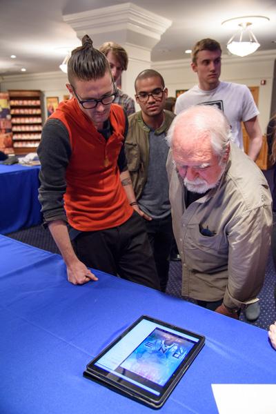 Larry Elmore reviewing Killian McKeown's portfolio.