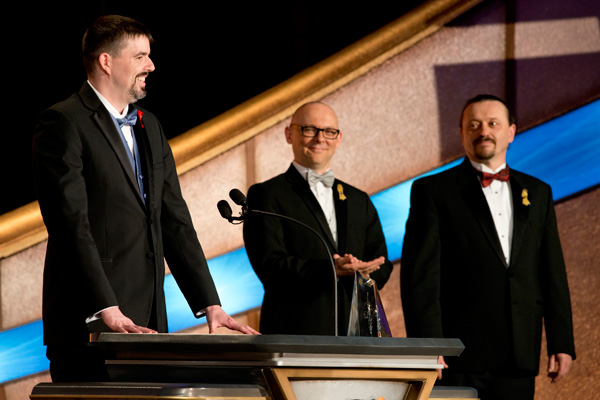 Daniel J. Davis on stage accepting his award with presenters Sean Williams and Sergey Poyarkov
