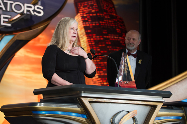 Sharon Joss on stage accepting the 2015 Golden Pen award with David Farland looking on.