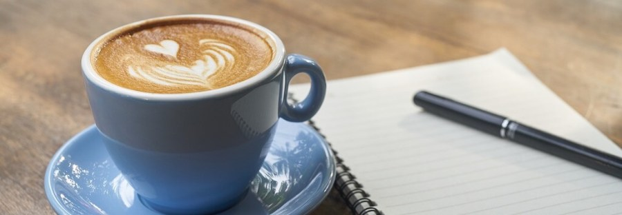 Notepad, pen and a cup of coffee
