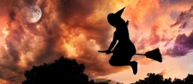 Witch flies at Halloween dusk searching for her cat...