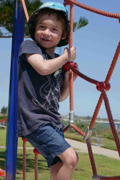 child boy playing on swings at park