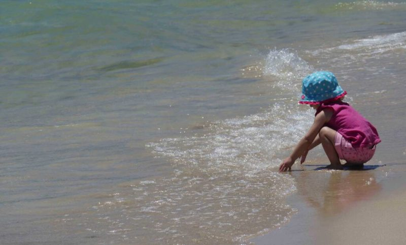 girl playing in water at the beach