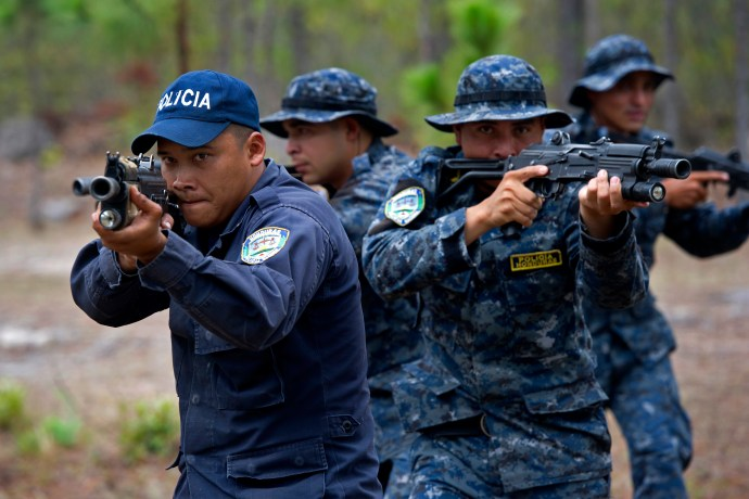 TIGRES Commandos conduct bounding over watch exercises during training with Green Berets from 7th Special Forces Group (Airborne) and Junglas from the Columbian National Police Tegucigalpa, Honduras., May. 08, 2014. 7th Special Forces Group (Airborne) Green Berets and Junglas from the Columbian National conduct daily physical training with TIGRES (Toma Integral Gubermental de Repuesta Especial de Seguridad) commandos to condition their bodies for the physical challenges they may encounter. The TIGRES will be the force of choice for the Honduran government with seeking to capture high value targets such as narcotraffiking and criminal leadership.(U.S. Army photo by Spc. Steven K. Young/Released)