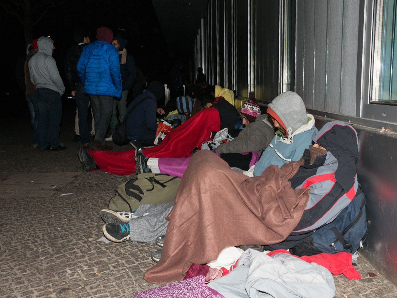 It's 21:00 at LaGeSo: refugees sit less than ten meters from the place where candles have been lit. They have wrapped themselves in blankets to survive the night in freezing temperatures