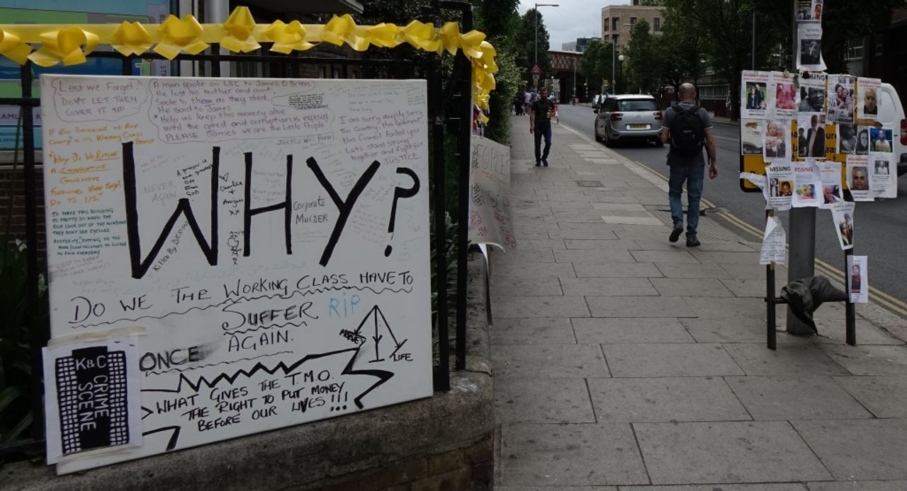 Placard reading, 'Why do we, the working class, have to suffer once again?' On the lamp post are photos put up by residents of missing people from the fire