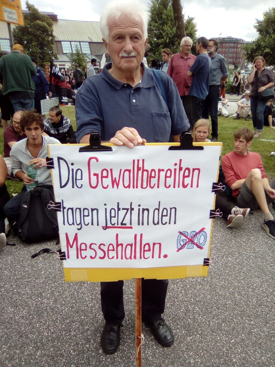 Eugen, with a sign reading: 'Those preparing violence are currently meeting in the exhibition centre'