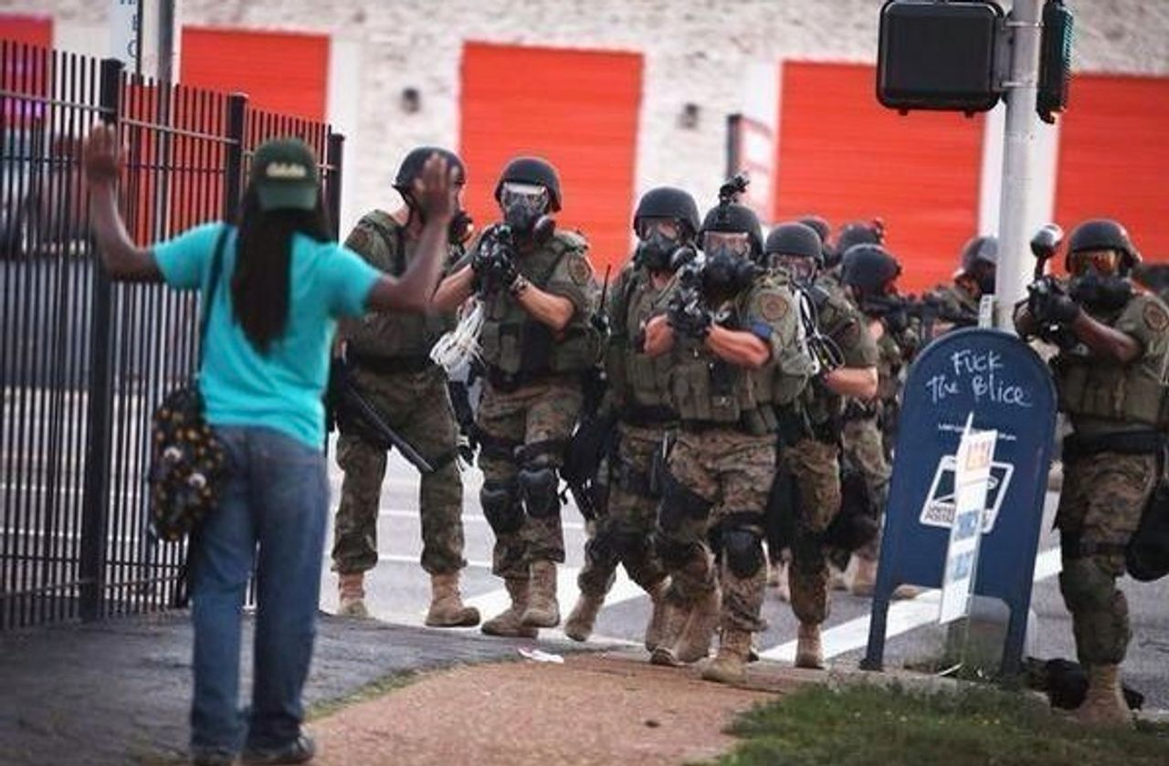 A squad of police aim automatic weapons at a young resident of Ferguson, Missouri