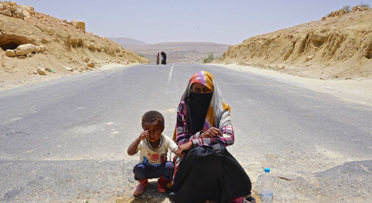 Suad, aged 18, begs in the middle of the road between Yemen's capital, Sana'a, and Saada with her four-year-old nephew, whose mother was killed by the Saudi war on Yemen - Credit: Giles Clarke/United Nations Office for the Coordination of Humanitarian Affairs (OCHA)