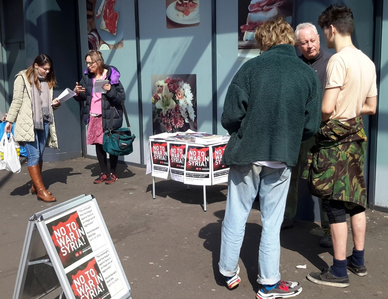 People discuss the military strikes in Syria at the Socialist Equality Party stall in Manchester