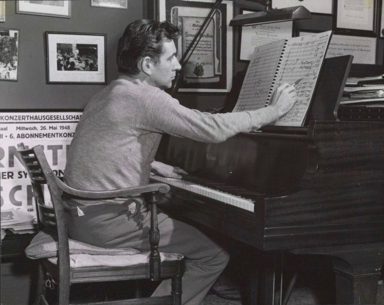 Leonard Bernstein working on a score at his piano, 1956