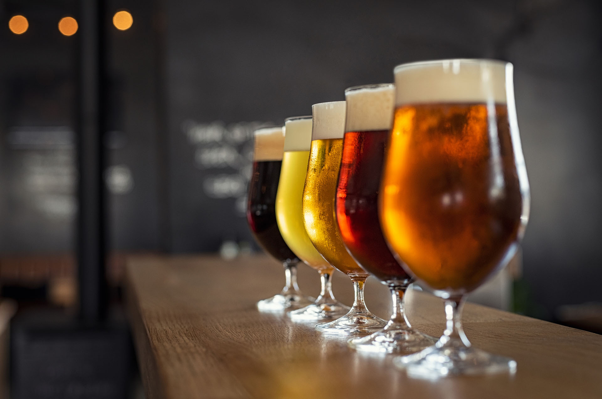 Glasses with different sorts of craft beer on wooden bar. Tap be_1559674428526