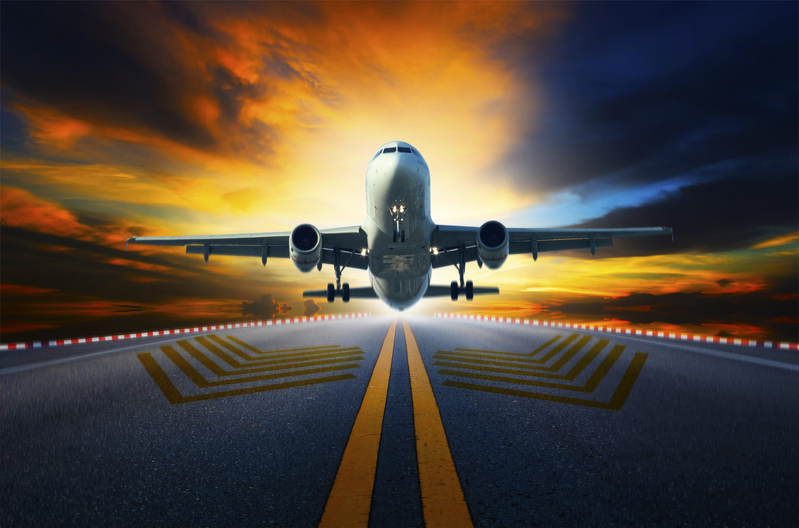 passenger jet plane preparing to take off from airport runways with motion blur against beautiful dusky sky