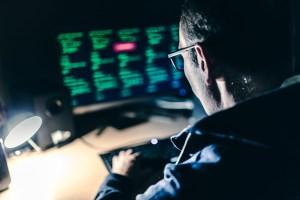 Computer hacker in a dark room