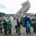 Truck offloading sand to an empty space in Westlake village for the community whose shacks were flooded