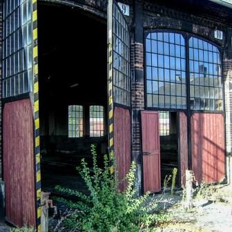 """Lokschuppen """"Haus 1"""" - Büsche bewachsen die Einfahrt. Das Bild entstand 2006. Inzwischen wurde hier aufgeräumt."""