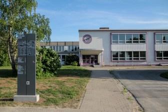 Das ehemalige High-School-Gebäude mit einem Wegweiser der Universität. Die Architektur vieler Gebäude ist typisch für die ausgehenden 1950er Jahre.