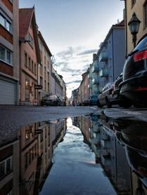 Blick durch die in einer Pfütze gespiegelten Büttnerstraße.