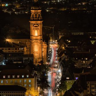 Straßenverkehr und Neubaustraße bei Nacht.
