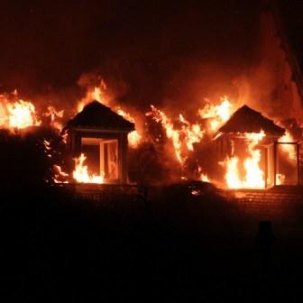 Aus den Fenstern im Dachstuhl lodern die Flammen.